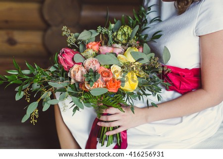 wedding bouquet of flowers roses with red ribbons in hands of the bride