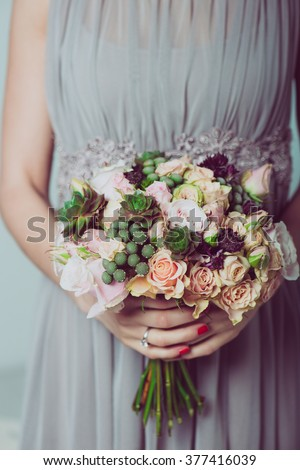 Wedding bouquet of flowers, young bride holding a bouquet of flowers. Image of wedding dress and floral bouquet. - stock photo