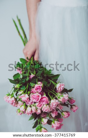 Wedding bouquet of flowers, young bride holding a bouquet of pink roses. Image of wedding dress and pink bouquet. - stock photo