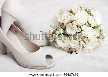 Wedding bouquet of pink and white roses and bride's shoes - stock photo