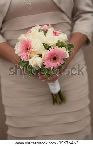 Wedding bouquet of pink daises and roses held by bride or bridesmaid - stock photo