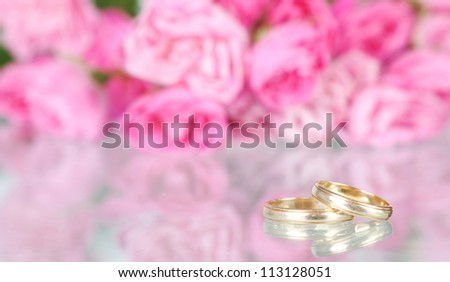 Wedding bouquet of pink roses and golden rings - stock photo