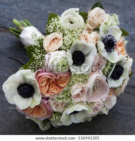 Wedding bouquet of pink roses and white anemone and pink ranunculus lying on wooden floor - stock photo