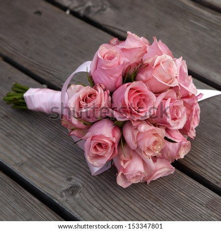 wedding bouquet of pink roses lying on wooden floor - stock photo