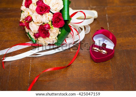 Wedding bouquet of red and cream roses lying on wooden floor.