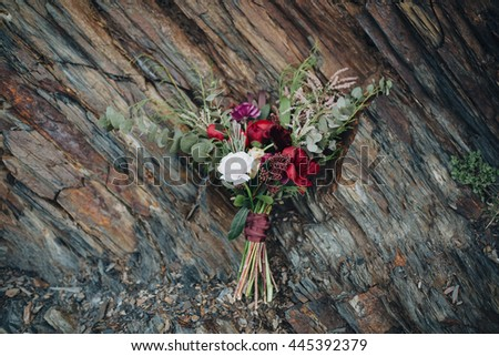 Wedding bouquet of red, white flowers and greenery stands near textured rocks in the mountains