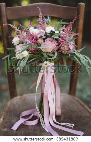 wedding bouquet of roses and berries with purple heather, lace, ribbons and brooch stand on vintage brown wooden chair outdoors in the garden - stock photo