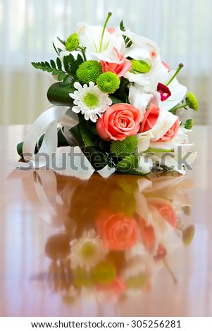 Wedding bouquet of roses and lilies for bride at a wedding party. Wedding bouquet of roses and lilies on the table against the background of a bright window. - stock photo