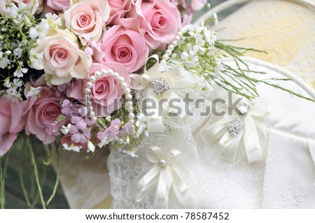 Wedding bouquet of roses and pearl necklace.