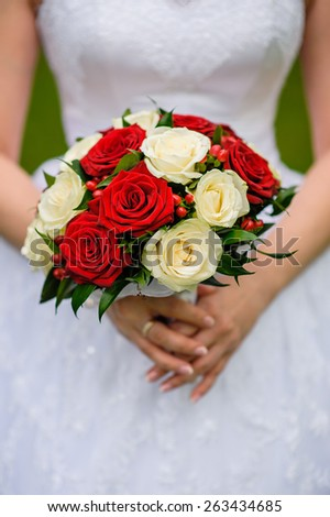 Wedding bouquet of roses in hands of the bride. - stock photo