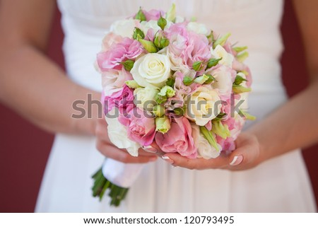 wedding bouquet of roses in the hands of the bride - stock photo