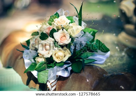 wedding bouquet of the bride and yellow roses lies on the edge of the fountain with the water splashing - stock photo