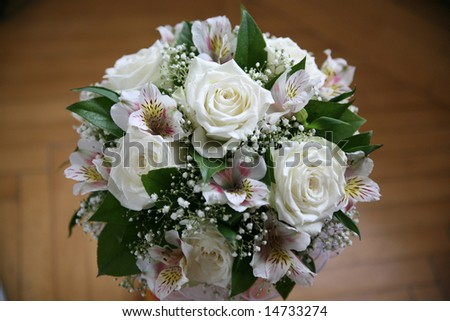 Wedding bouquet of the bride from white roses on a background of pink gentle flowers
