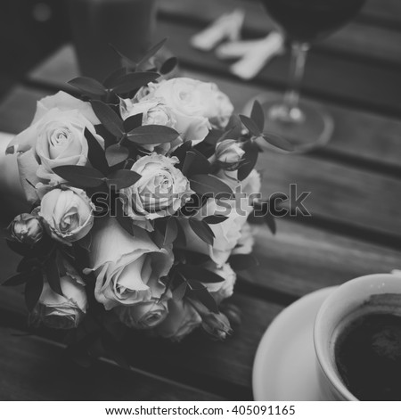 wedding bouquet of tiny roses  laying on wooden table in cafe between coffee cappucino and glass of vine