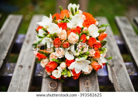 Wedding bouquet of white and orange roses and with two wedding rings at bench - stock photo