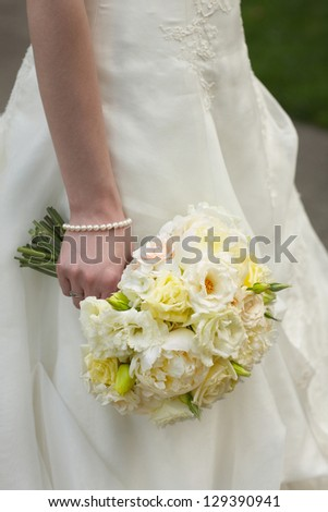 Wedding bouquet of white and yellow roses held by bride - stock photo