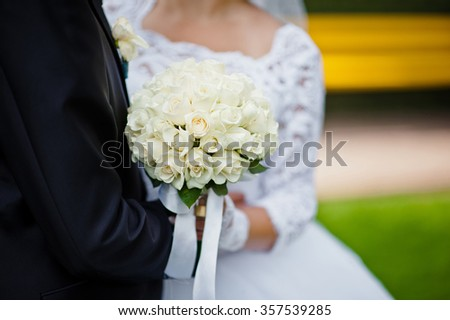 Wedding bouquet of white rose in hands of newlywed - stock photo