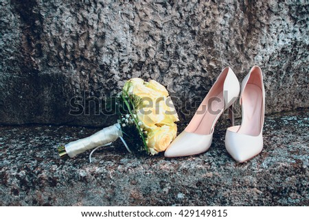 Wedding bouquet of white roses and bride shoes on natural stone background. wedding concept - stock photo