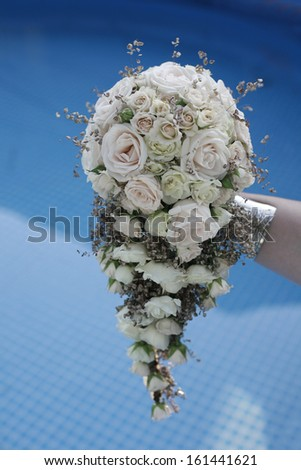 Wedding bouquet of white roses in front of blue background , wedding bouquet - stock photo