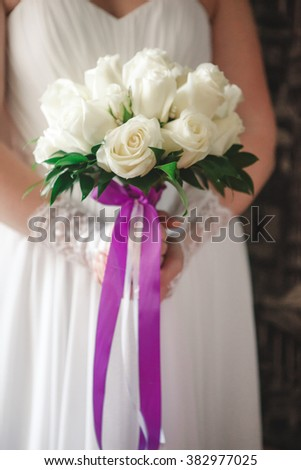 wedding bouquet of white roses in hands of bride with purple ribbon