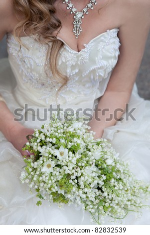 wedding bouquet of white small flowers lily-of-the-valley at girl's hand - stock photo