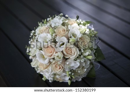Wedding bouquet of yellow and cream roses lying on wooden black floor - stock photo