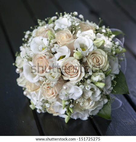 Wedding bouquet of yellow and cream roses lying on wooden floor - stock photo