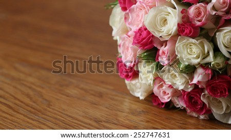 Wedding bouquet of yellow and pink roses lying on wooden background - stock photo