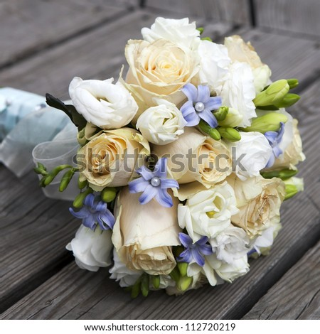 Wedding bouquet of yellow and white  roses and blue fresia  lying on wooden floor - stock photo
