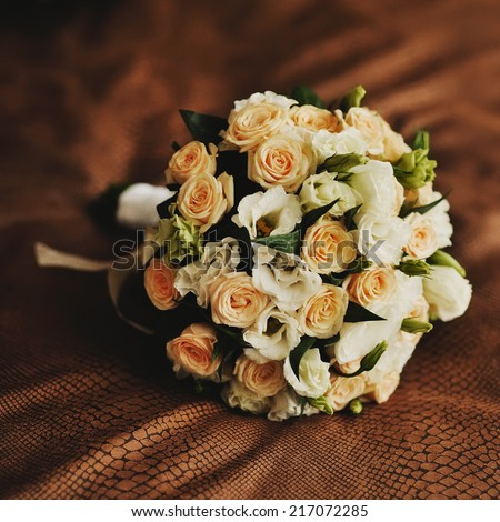 Wedding bouquet of yellow and white roses  lying on bed. - stock photo