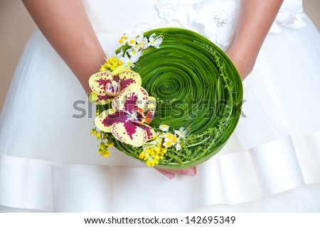 wedding bouquet of yellow orchid and green leaves - stock photo
