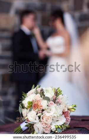 Wedding bouquet on a background of the bride and groom - stock photo
