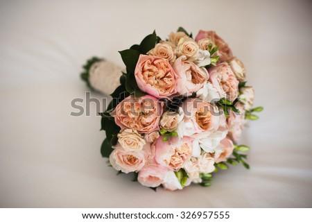wedding bouquet on a white silken sheet - stock photo