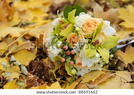 Wedding bouquet on bright autumn leaves in park. Soft focus.