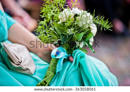Wedding bouquet on hand of bridesmaid on turquoise dress - stock photo
