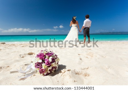 Wedding bouquet on wedding couple background, kissing at the beach - stock photo
