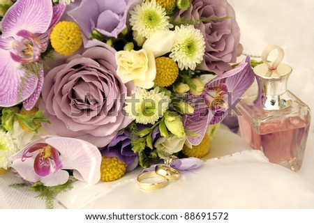 Wedding bouquet, rings and perfume bottle, soft focus.
