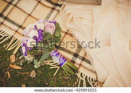 Wedding bouquet, the bride's bouquet. Bouquet of purple, lilac and white  flowers with a ribbon of purple color on grass and plaid