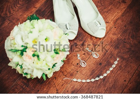 Wedding bouquet, white shoes and diamond jewelry on a wood background. Beautiful set of women's wedding accessories - stock photo