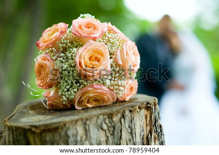 Wedding bouquet with bride and groom in background - stock photo