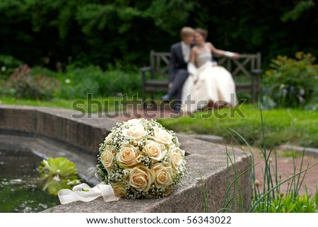 Wedding bouquet with bride and groom in background. Shallow DOF - stock photo