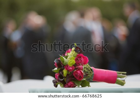 Wedding bouquet with party in background, DOF focus on flowers - stock photo
