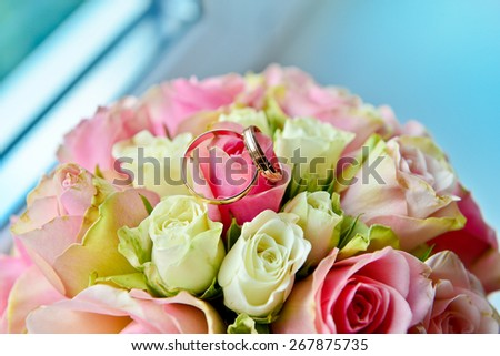 Wedding bouquet with pink and white roses. Wedding day. Wedding decorations. Gold wedding rings.  - stock photo