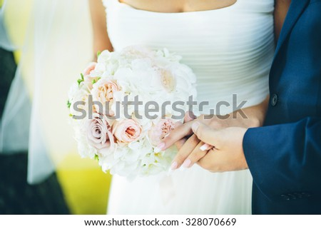 wedding bouquet with pink flowers in hands of the groom and bride