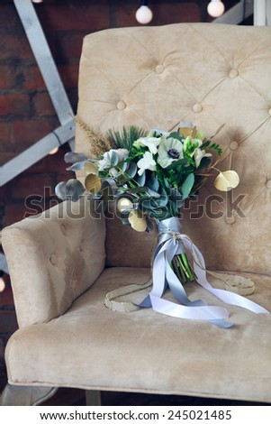 Wedding bouquet with ranunculus, freesia, roses and white anemon on the armchair