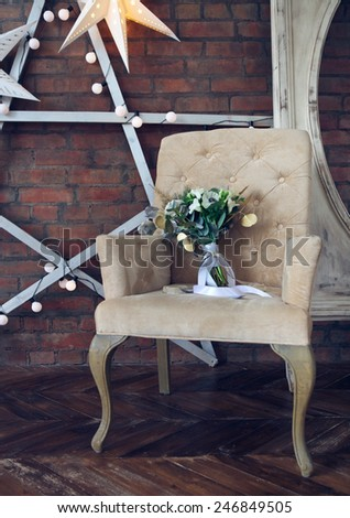 Wedding bouquet with ranunculus, freesia, roses and white anemon on the armchair - stock photo