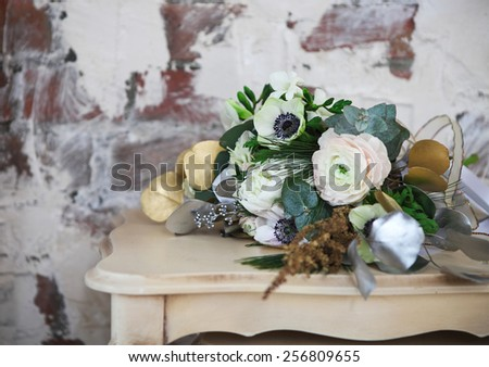 Wedding bouquet with ranunculus, freesia, roses and white anemon on the table