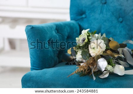 Wedding bouquet with ranunculus, freesia, roses and white anemone on the blue armchair - stock photo