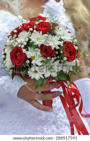 Wedding bouquet with roses and daisies in hand of the bride - stock photo