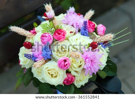 Wedding bouquet with roses on a wooden bench